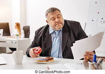 Busy engaged employee eating at his workplace - Combining...