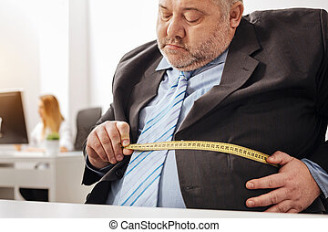Concerned overweight office worker taking measurements -...