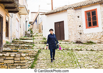 Stylish woman walking around old town. Female outdoors -...