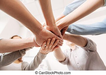 Close up of coworkers hands being united - One team. Happy...