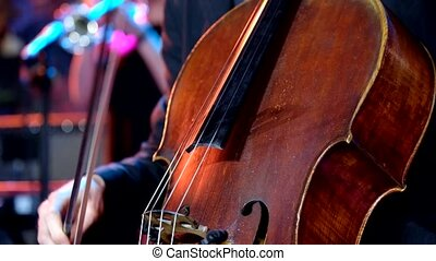 Man plays a cello on stage