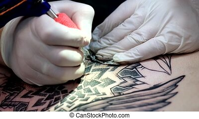 Artist is making the tattoo close up - Artist is making a...