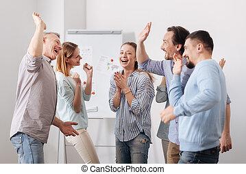 Happy woman standing between her colleagues - Be joyful....