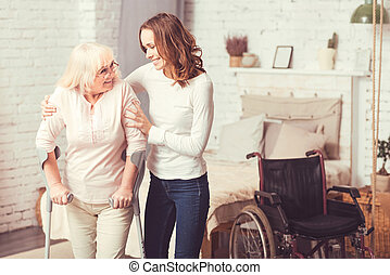 Merry young woman helping disabled old lady at home