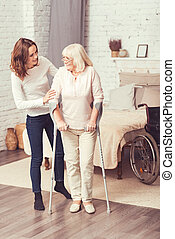 Helpful young woman helping disabled old mother at home