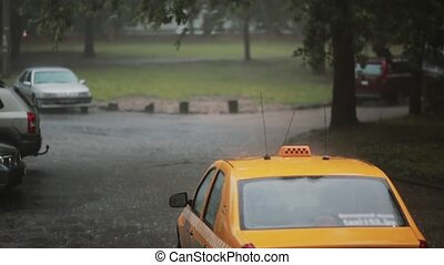 Rain pouring on cars and a taxi in the street with sound....