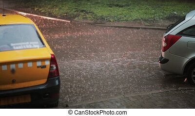 Rain pouring down on pavement, a taxi and a car turns into flood. Another car passes by, water under it splashes around