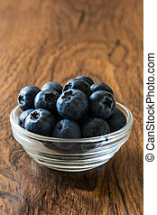 Blueberries in crystal bowl on wooden background