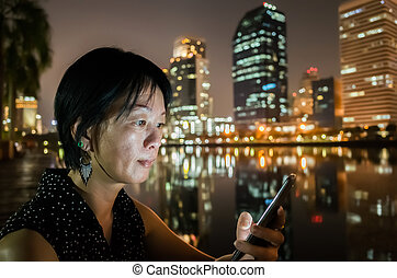 woman using cellphone - asian woman using cellphone in the...