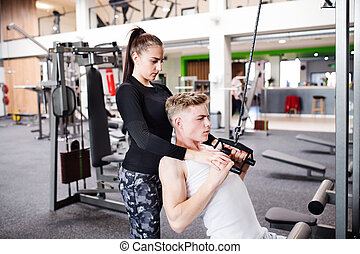 Fit young man in gym working out on pull-down machine. -...