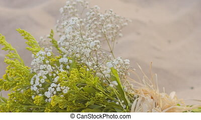 Bouquet of wild flowers on the sand