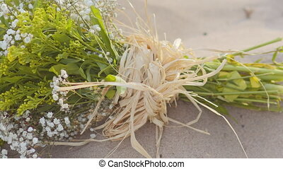 a bouquet of wild flowers on the sand
