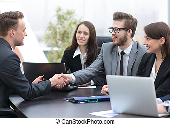 Business people shaking hands, finishing up a meeting - Two...