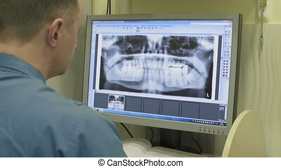 Dentist carefully looks at teeth X-rays at computer monitor...
