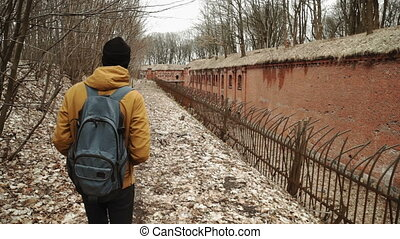 A young man With backpack on back walks through the park in...