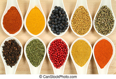 Colorful spices - Spices and herbs in white ceramic bowls....