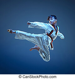 Young boy training karate on blue background - Young boy...