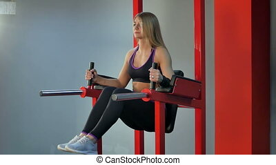 Young blonde woman doing press exercise in the gym