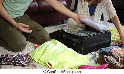 Couple packing clothes into suitcase for journey - Closeup...