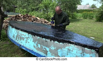 man brush with resin an old boat bottom in garden outdoor....
