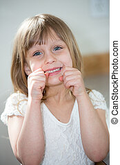 Little girl flossing teeth.