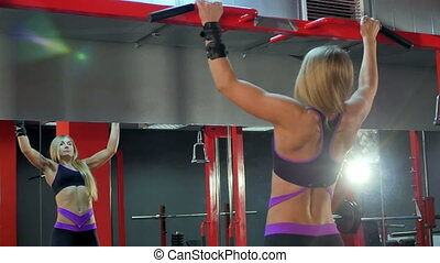 Blonde sporty woman doing pull ups at the gym