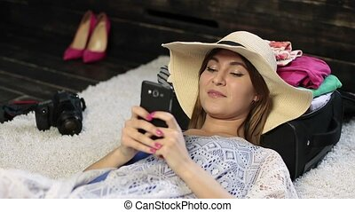 Woman lying on floor text messaging on cell phone - Closeup...
