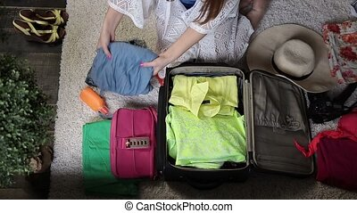 Female hands packing clothes into travel bag - Top view of...
