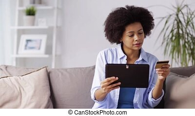 happy woman with tablet pc and credit card at home - people,...