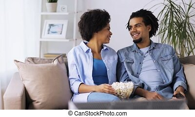 smiling couple with popcorn watching tv at home