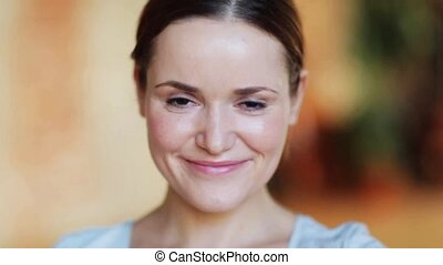 face of happy smiling young woman - people, emotion and...