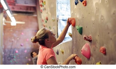 young woman exercising at indoor climbing gym wall -...