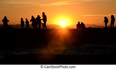 People waiting for the sunset - Group of people waiting for...