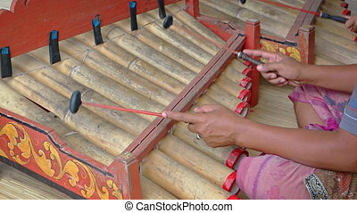 Local musicians play traditional, bamboo percussion pipes in...