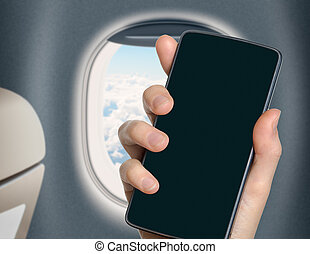 hand with blank mobile phone in airplane or jet interior -...