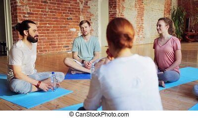 group of people resting on yoga mats in gym - fitness, sport...