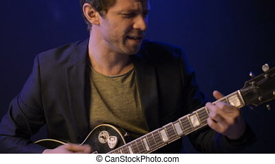 A man plays an electric guitar and sings in a dark room - A...
