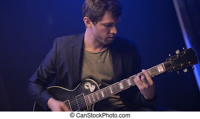 A man plays an electric guitar and sings in a dark room