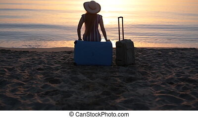 Young woman sitting on suitcase on a beach