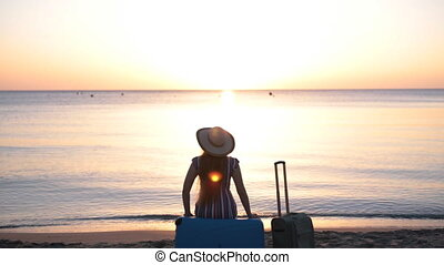 Young woman sitting on suitcase on a beach - Young woman...