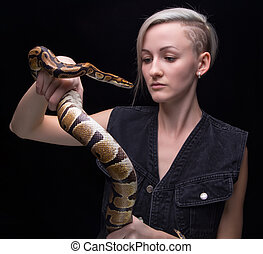 Blond woman holding python on black background