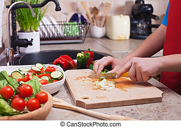 Child hands chopping vegetables on cutting board - the spring oniopns