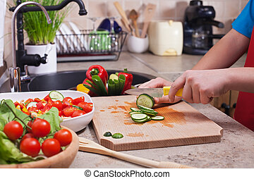 Child hands chopping vegetables on cutting board - slicing the cucumber
