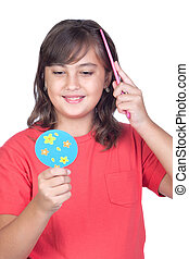Preteen girl combing with a comb in front of a mirror...