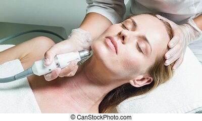 Professional beautician massaging female face by device -...