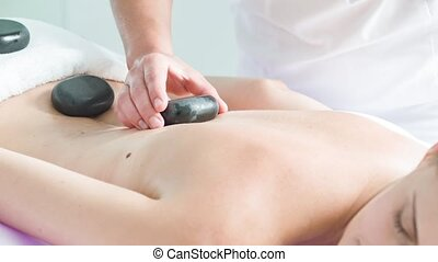Skillful beautician massaging female body by stones
