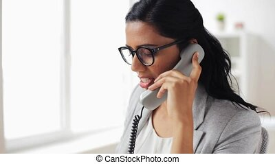 businesswoman calling on phone at office - business,...