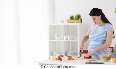 pregnant woman cooking vegetable salad at home - healthy...