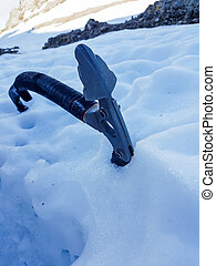 Closeup of ice axe on steep slope. Ascending snow covered...