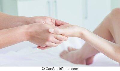 Professional masseuse massaging wrist of woman